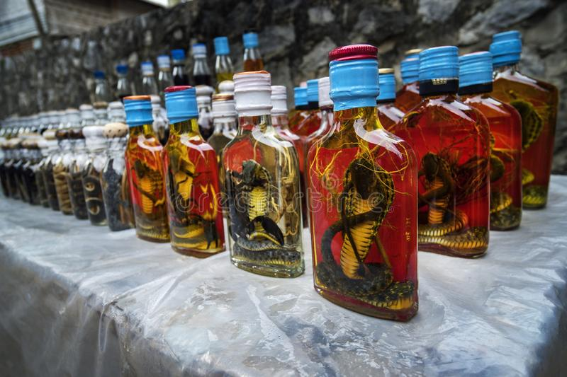 Bottle of Alcohol containing liquor with cobra snake and scorpion inside on a market royalty free stock image