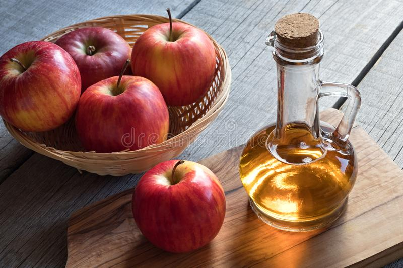 A bottle of apple cider vinegar with apples in a basket. A bottle of apple cider vinegar with apples in the background stock photos