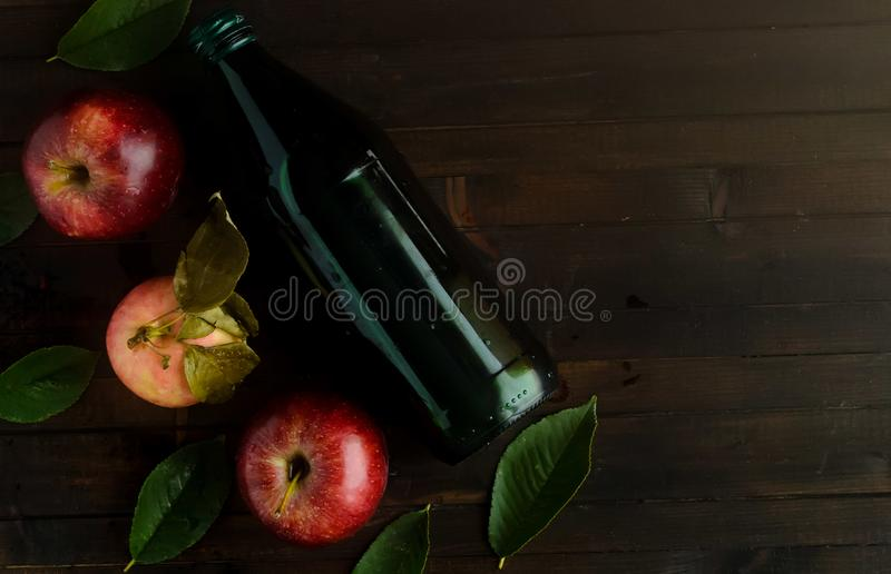 A bottle of a apple cider vinegar with three fresh apples and green leaves. stock photos