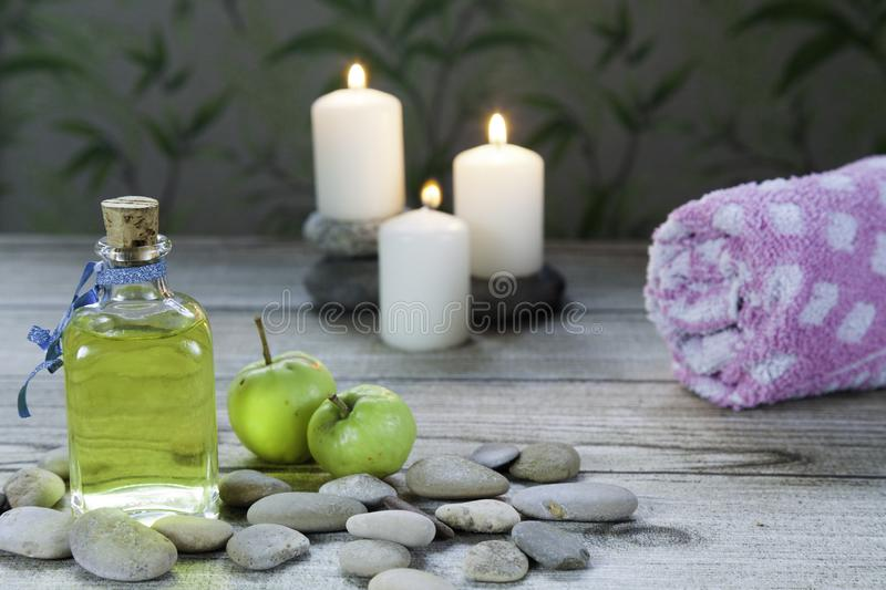 Bottle of apple oil massage, river pebbles, towel and three lighted candles on wooden table and herbal. Bottle of apple oil massage, river pebbles, two small stock photos