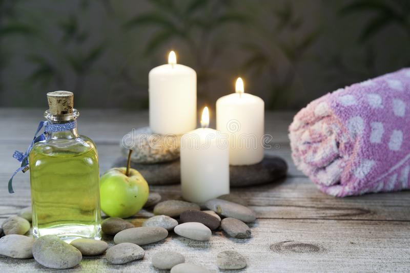 Bottle of apple oil massage a small green apple, towel and three lighted candles on wooden table and herbal. Bottle of apple oil massage, river pebbles, a small royalty free stock images