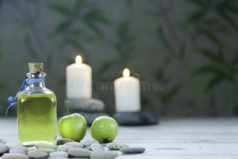 Bottle of apple oil , river pebbles, two small green apples and two lighted candles on wooden table and herbal background. Bottle of apple oil massage, river stock images