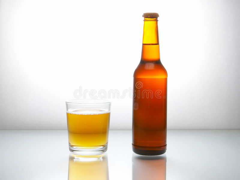 Bottle with beer. And a glass filled with beer with foam on a white reflecting surface stock photography