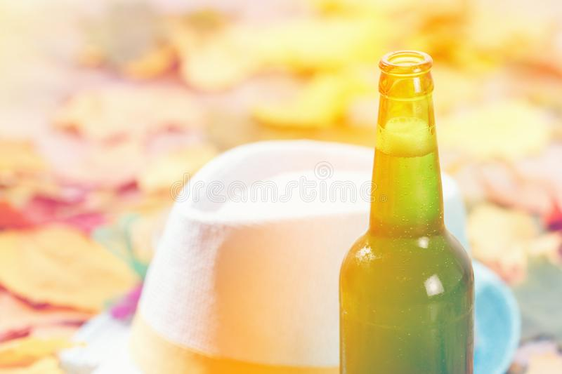 Bottle of Beer glass pint octoberfest picnic on natural background with hat and autumn leaves. Bottle of Beer glass pint octoberfest picnic on natural background royalty free stock image