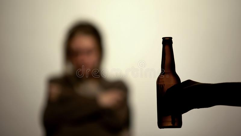 Bottle of beer in hand offering to drink alcohol, addicted woman on background royalty free stock photo