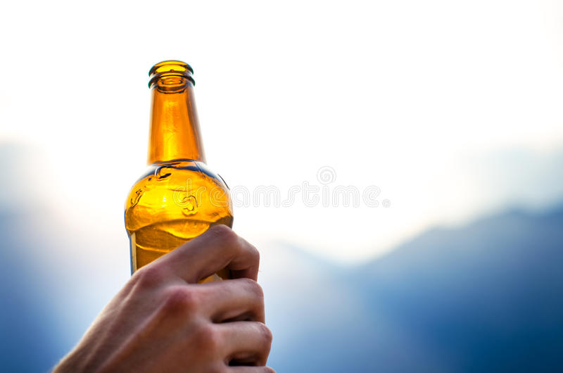 Bottle of beer. Natural background. Man hand´s keep a bottle of beer. Alcohol drink. stock image