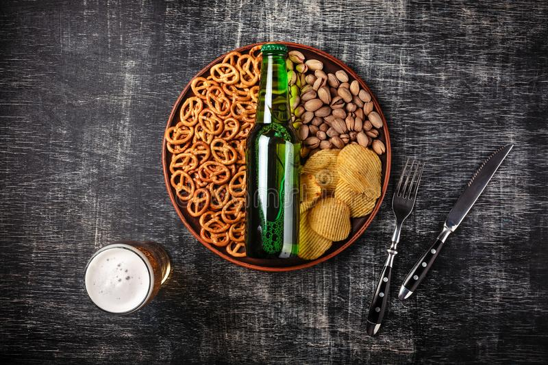 A bottle of beer on a plate with salted ookies pretzels, pistachio nuts and chips on a black scratched chalk board. Top view royalty free stock photos