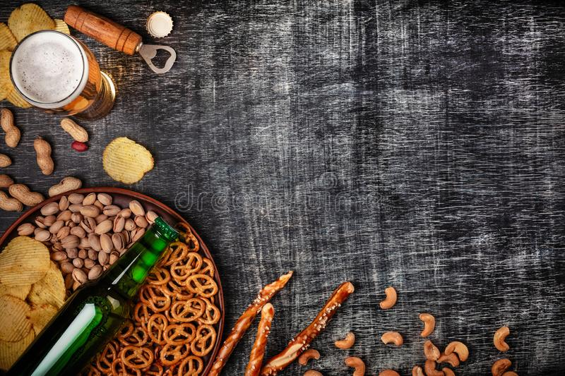 A bottle of beer on a plate with salted ookies pretzels, pistachio nuts and chips on a black scratched chalk board. Top view stock photo