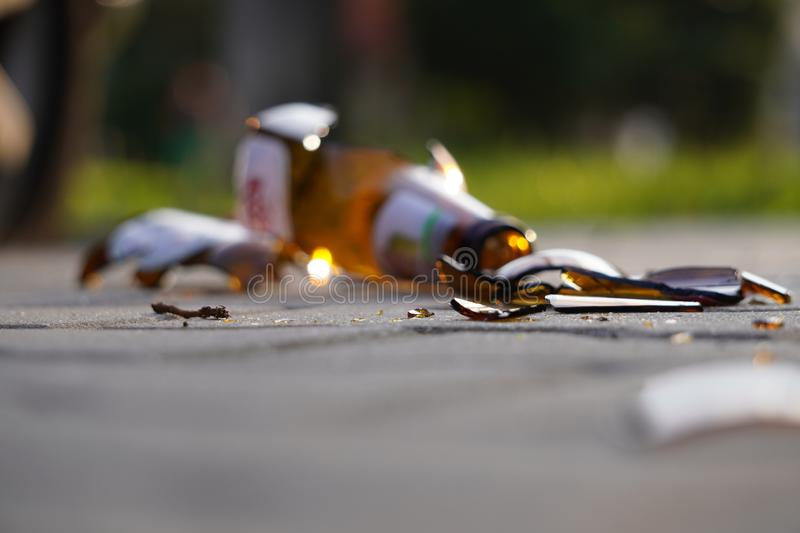 Bottle of beer, soda or drugs from dark glass is broken. Shattered beer bottle on ground in sunset light. Fragments of glass on royalty free stock photography