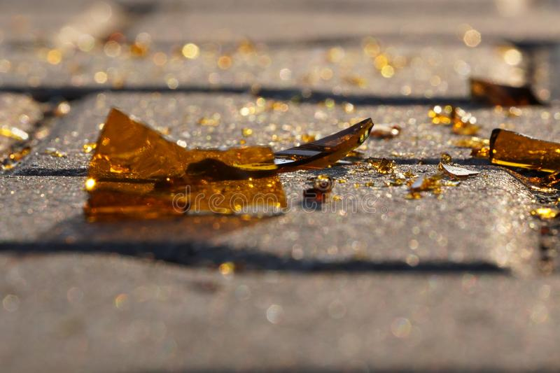 Bottle of beer, soda or drugs from dark glass is broken. Shattered beer bottle on ground in sunset light. Fragments of glass on royalty free stock photos