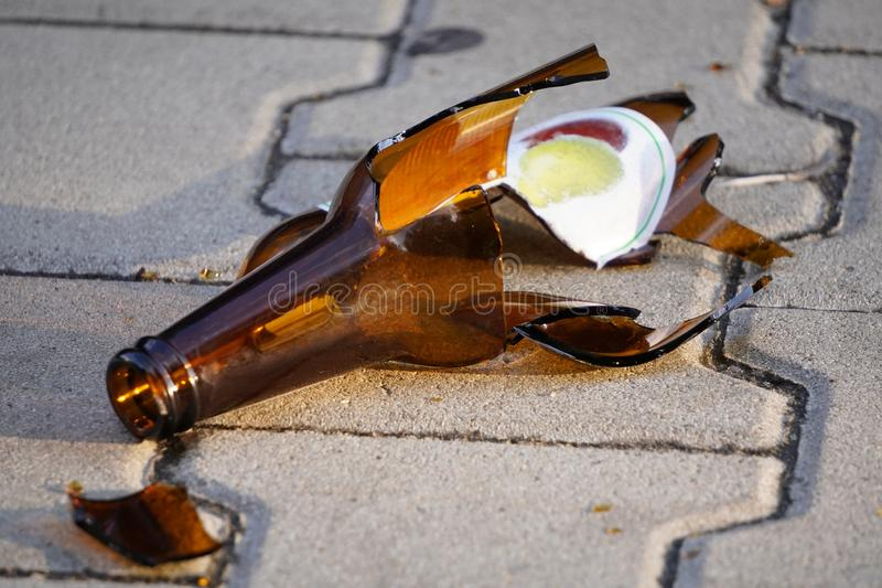 Bottle of beer, soda or drugs from dark glass is broken. Shattered beer bottle on ground in sunset light. Fragments of glass on stock images