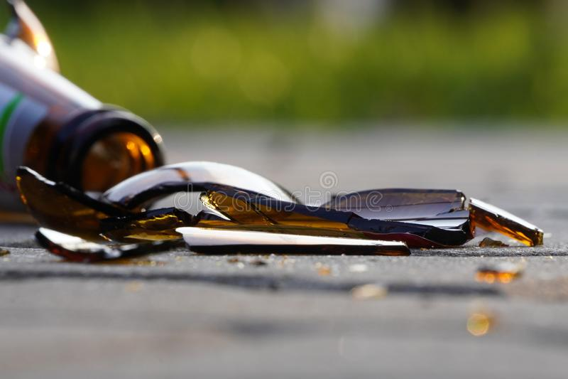Bottle of beer, soda or drugs from dark glass is broken. Shattered beer bottle on ground in sunset light. Fragments of glass on stock image