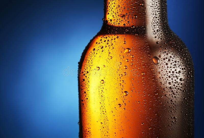 Bottle of beer with water drops. Bottle of beer with drops on a blue background. Close up part of the bottle stock image