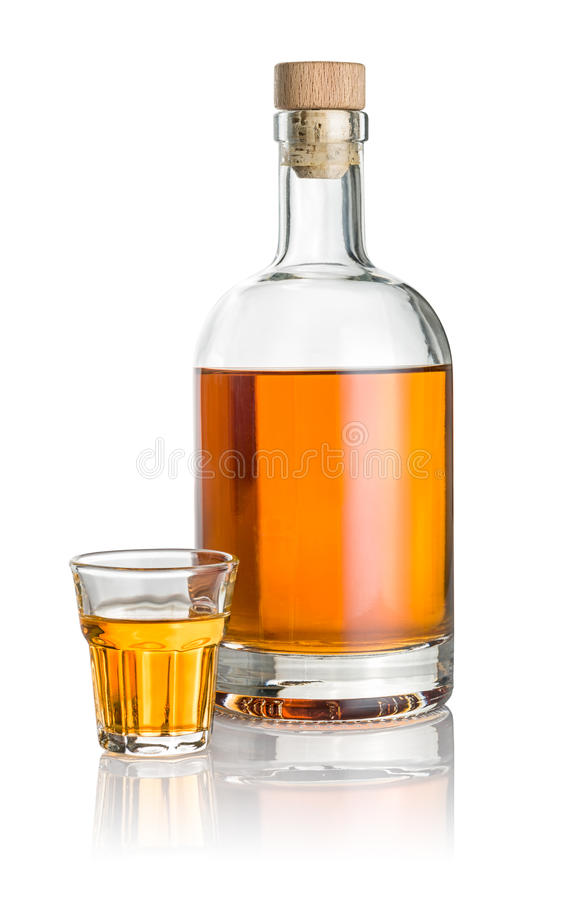 Bottle and beveled shot glass filled with amber liquid. A bottle and beveled shot glass filled with amber liquid stock photography