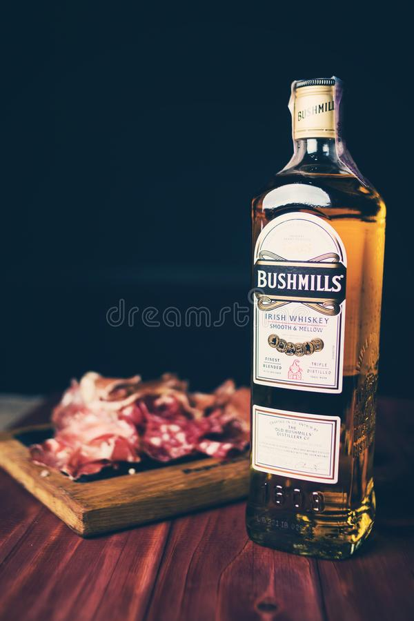 Bottle of Bushmills with snack. KIEV, UKRAINE - OCT 18, 2018: Bottle of Bushmills Original Irish whiskey, product of Old Bushmills Distillery founded in 1608 royalty free stock photos