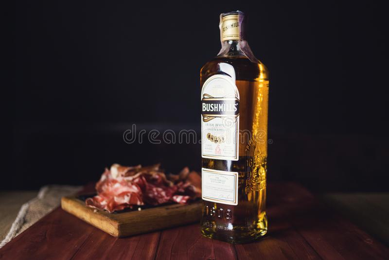 Bottle of Bushmills with snack. KIEV, UKRAINE - OCT 18, 2018: Bottle of Bushmills Original Irish whiskey, product of Old Bushmills Distillery founded in 1608 stock image