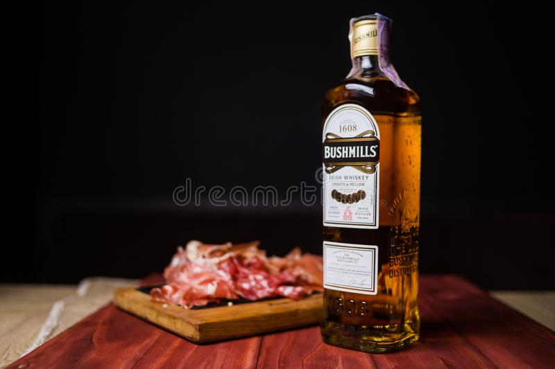 Bottle of Bushmills with snack. KIEV, UKRAINE - OCT 18, 2018: Bottle of Bushmills Original Irish whiskey, product of Old Bushmills Distillery founded in 1608 stock photos