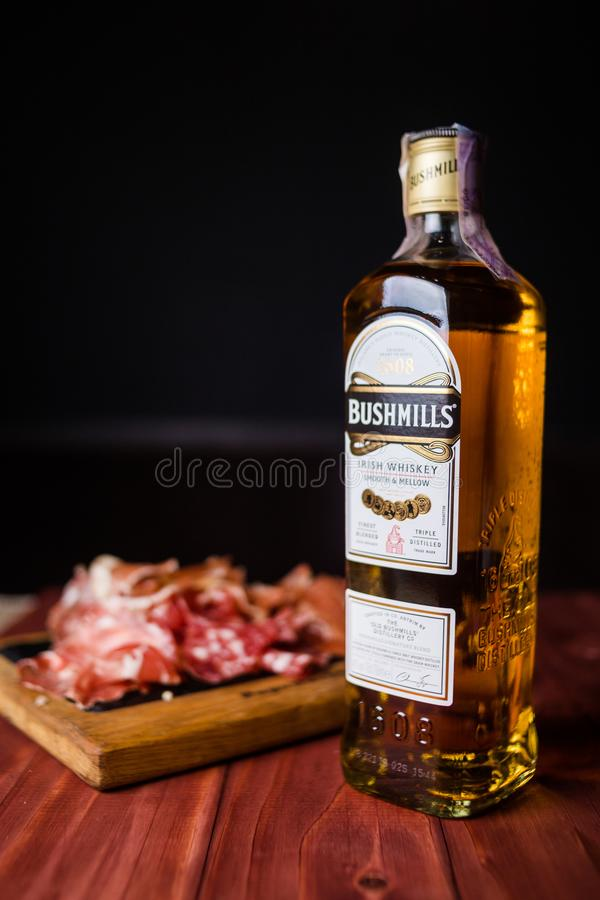 Bottle of Bushmills with snack. KIEV, UKRAINE - OCT 18, 2018: Bottle of Bushmills Original Irish whiskey, product of Old Bushmills Distillery founded in 1608 royalty free stock photography