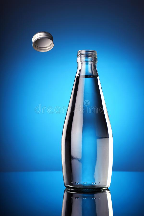 The Bottle Cap Challenge Concept - Fresh water in a bottle with open cap flying royalty free stock image