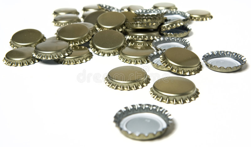 Bottle Caps. A variety of bottle caps lay on a white background royalty free stock photos