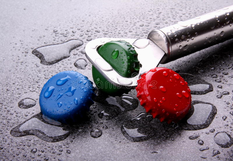 Bottle caps and opener. Details of bottle caps and a bottle cap opener with water drops royalty free stock photo