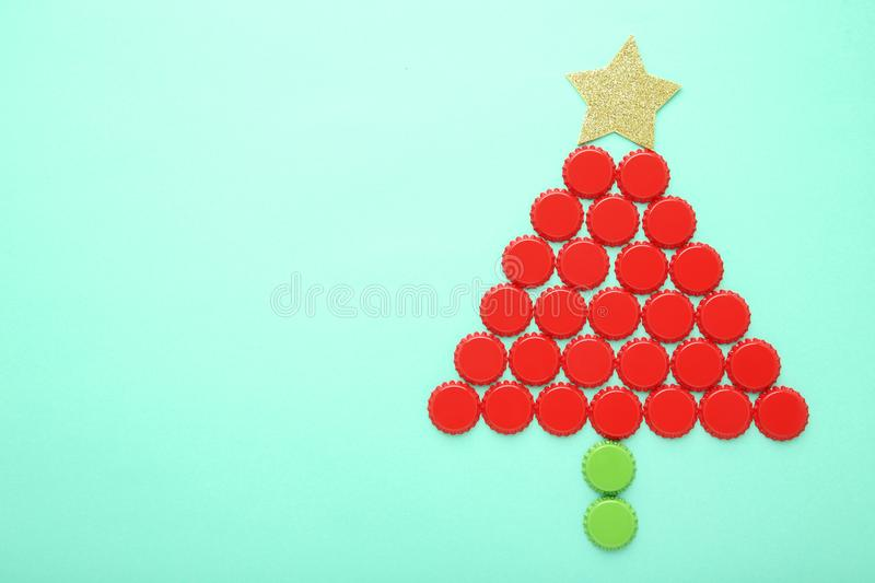 Bottle caps. In shape of christmas tree on mint background stock images