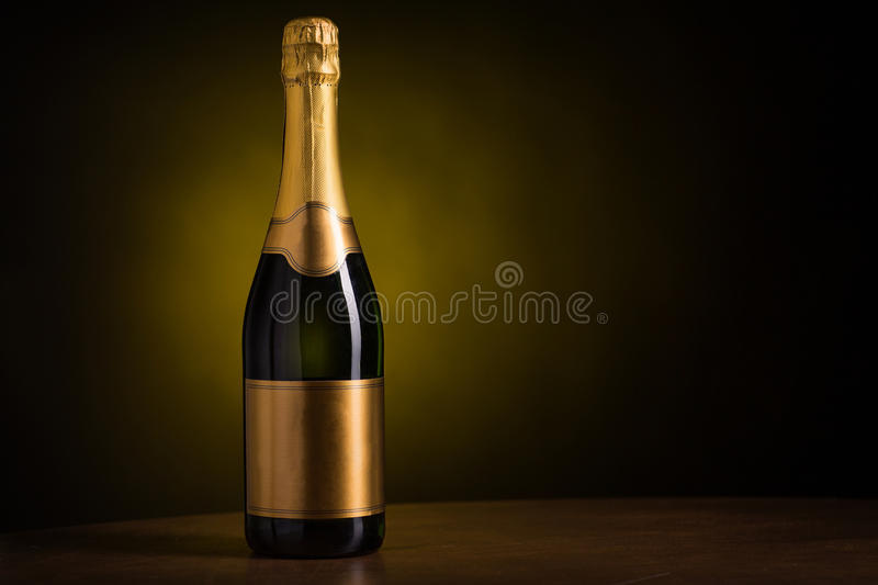 Bottle of champagne with blank golden label. Drink, alcohol, advertisement and holidays concept - bottle of champagne with blank golden label on wooden table royalty free stock image
