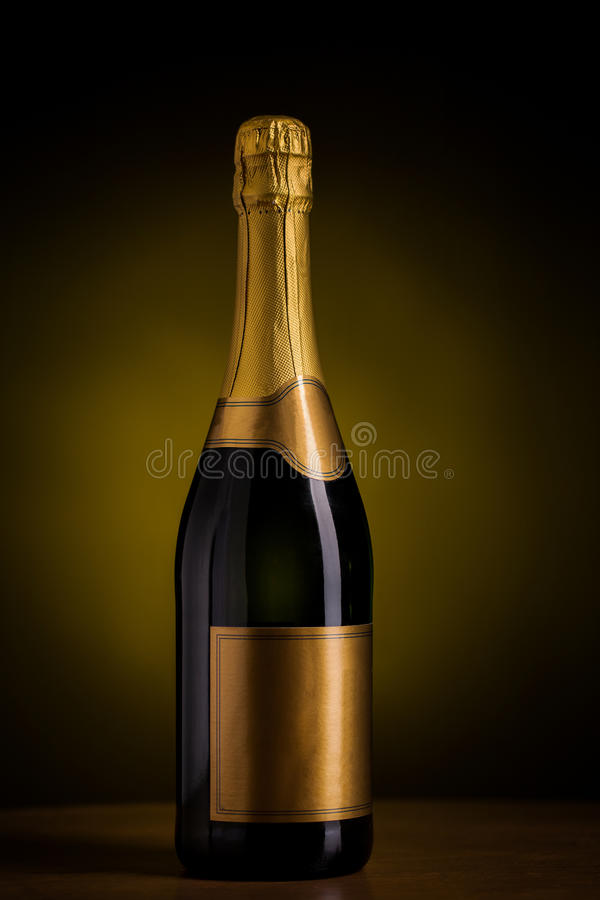 Bottle of champagne with blank golden label. Drink, alcohol, advertisement and holidays concept - bottle of champagne with blank golden label on wooden table stock photo