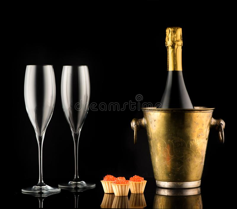 Bottle champagne in a bucket and caviar. On a black background stock photo