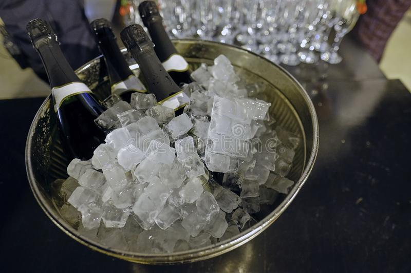 Bottle of champagne in bucket of ice. Bar counter. stock photos