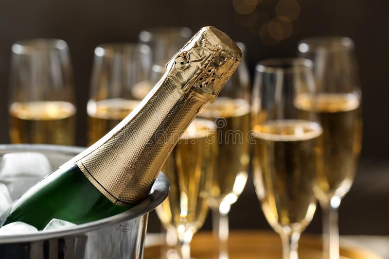 Bottle of champagne in bucket with ice and glasses on blurred background. stock photos