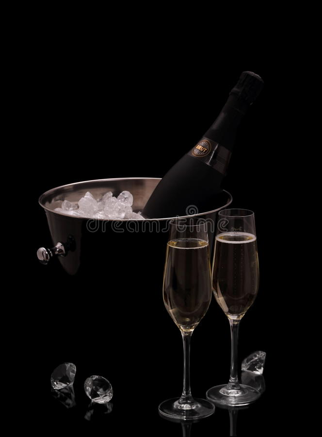 Bottle of champagne in bucket isolated with deco diamonds. Bottle of champagne in bucket isolated on black with deco diamonds royalty free stock photo