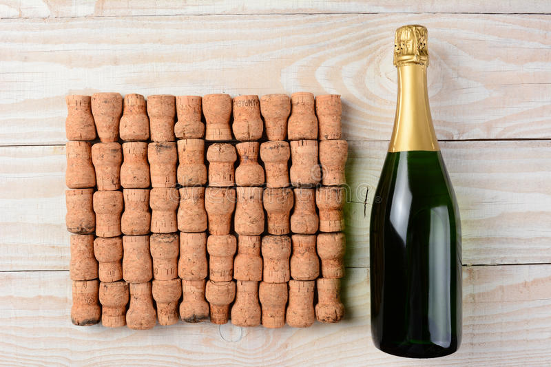 Bottle of Champagne and Corks. High angle shot of a bottle of champagne laying next to a large group of corks arranged in rows on a whitewashed wood table royalty free stock photography