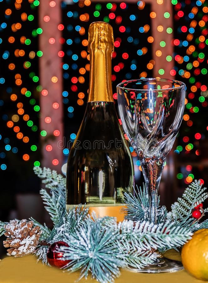 A bottle of champagne and a crystal glass on the background of a beautiful bokeh. royalty free stock photos