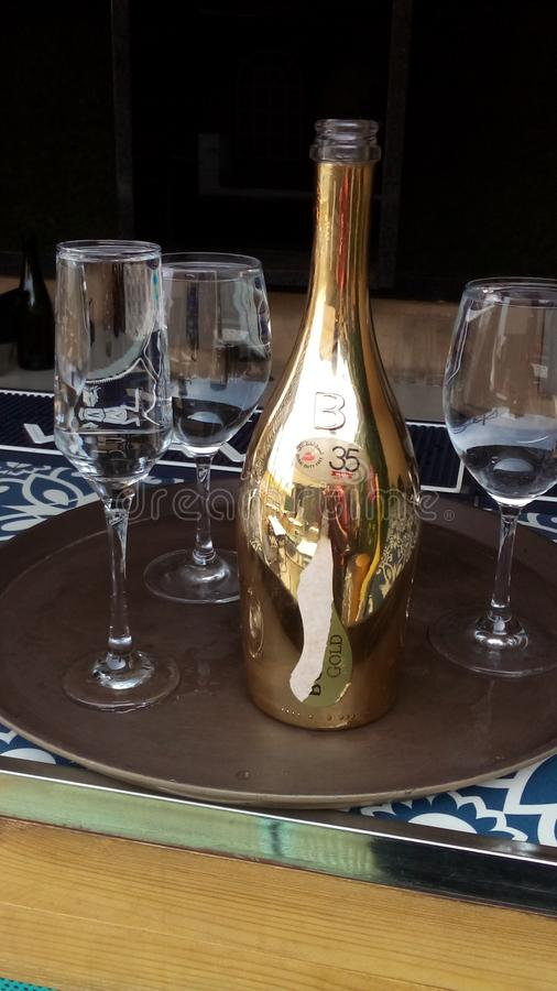 Bottle of champagne with glasses having water on it stock images