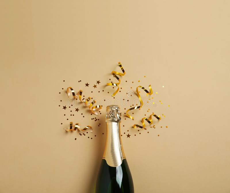 Bottle of champagne with gold glitter and confetti on beige background, flat lay. Hilarious. Celebration stock photos