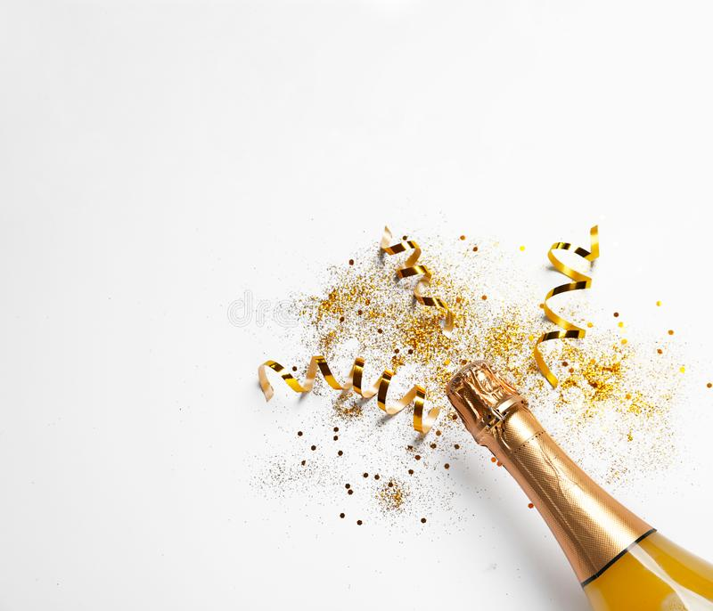Bottle of champagne with gold glitter, confetti on white background, top view. Hilarious celebration. Bottle of champagne with gold glitter, confetti and space royalty free stock image
