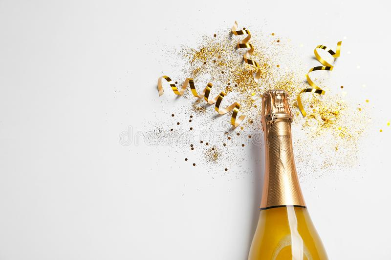 Bottle of champagne with gold glitter, confetti and space for text on white background, top view. Hilarious. Celebration royalty free stock photos