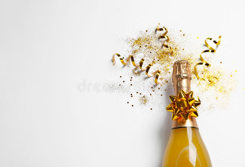 Bottle of champagne with gold glitter, confetti and space for text on white background, top view. Hilarious celebration royalty free stock photography