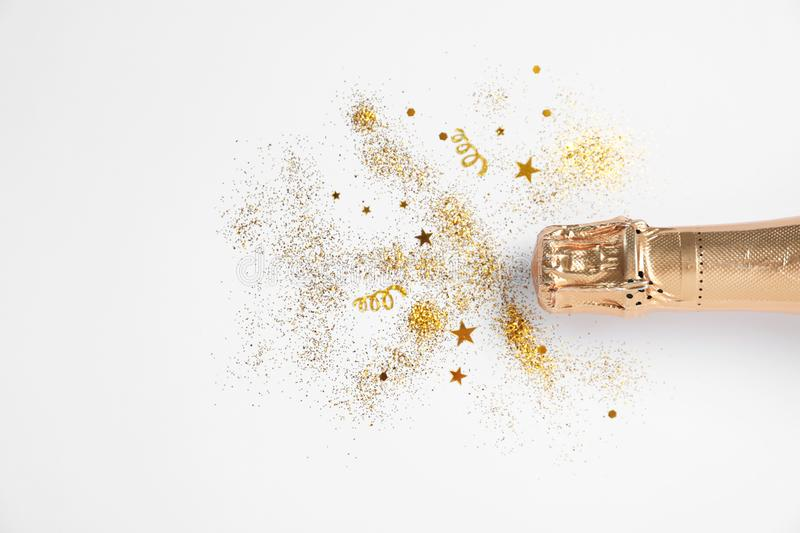 Bottle of champagne with gold glitter and confetti on white background, top view. Hilarious celebration stock photography