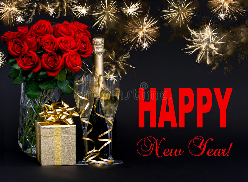 Bottle of champagne with golden fireworks and flowers stock photo