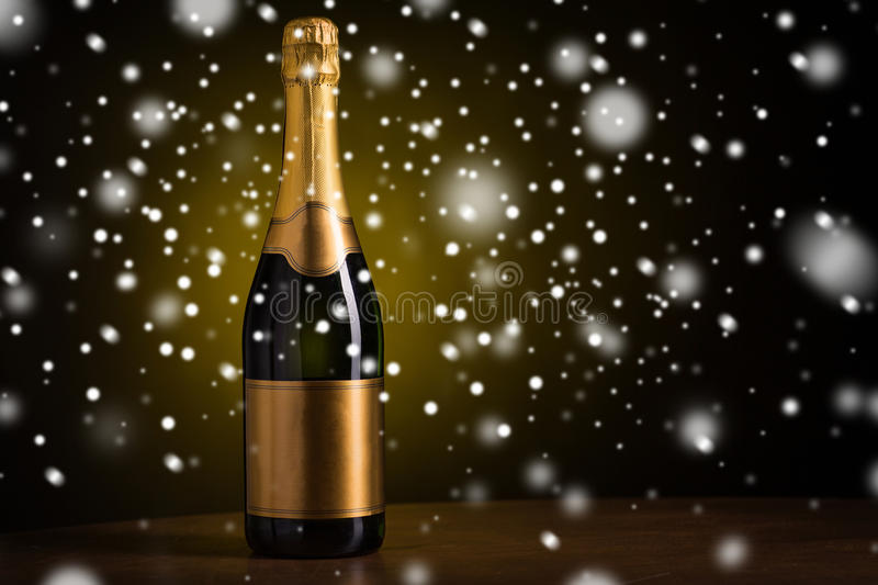 Bottle of champagne with golden label over snow. Drink, alcohol, christmas, new year and winter holidays concept - bottle of champagne with blank golden label on stock photography