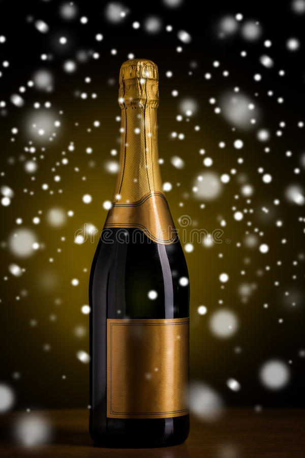 Bottle of champagne with golden label over snow. Drink, alcohol, christmas, new year and winter holidays concept - bottle of champagne with blank golden label on stock photo