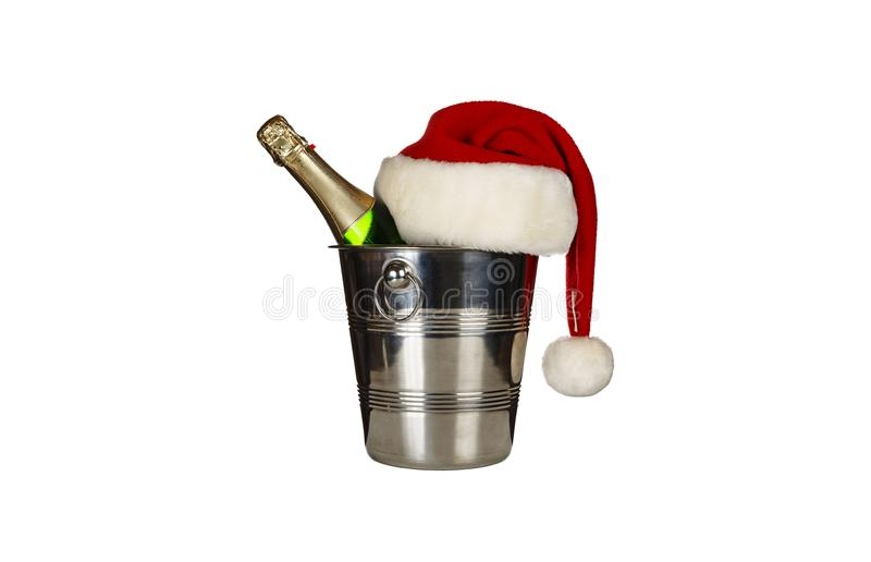 A bottle of champagne in an ice bucket and a Santa Claus hat isolated on white background stock image