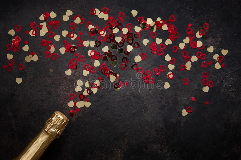 Bottle of champagne and pattern of red and gold hearts. Top view, close-up, flat lay on dark brown background stock photography