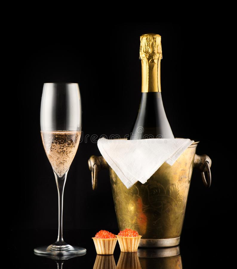 Bottle champagne and tartlets with red caviar stock photos