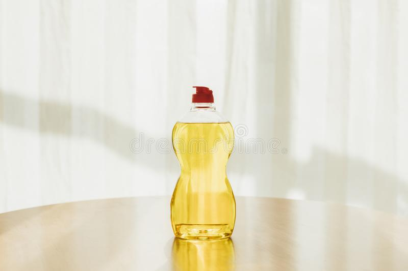 Bottle of cleaning fluid. Close-up view of plastic bottle of yellow cleaning fluid on tabletop royalty free stock image