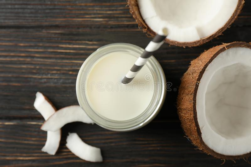 Bottle of coconut milk with straw, coconut and slice coconut on wooden background, space for text. Top view stock photo