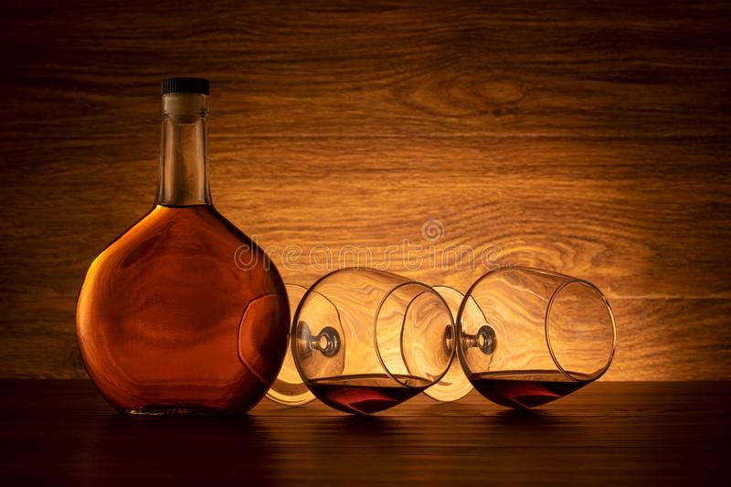 A bottle of cognac and two wine glasses on the table stock image