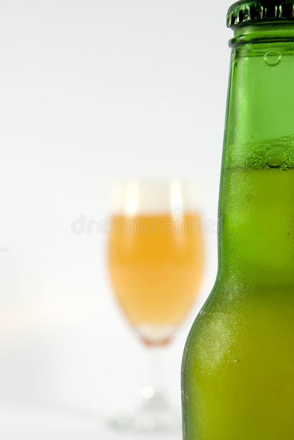 Bottle with cold beer. Focus on the cold bottle of beer and glass of beer in background royalty free stock image